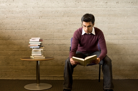Young man sitting and reading book